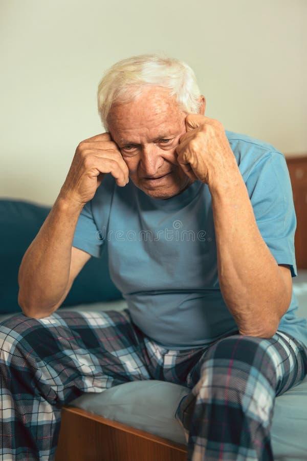 Älterer Mann, der auf dem Bett leidet unter Krise sitzt stockbild