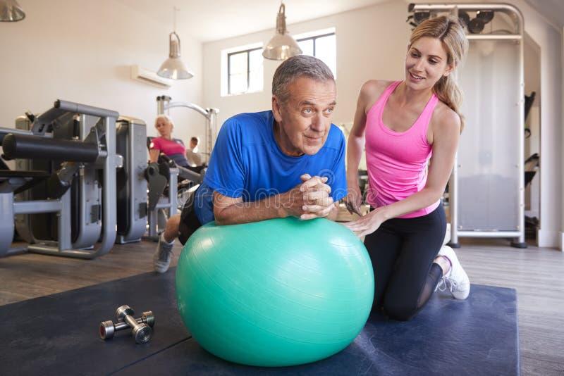 Älterer Mann, der auf dem Gymnastikball angeregt wird vom persönlichen Trainer In Gym trainiert lizenzfreie stockbilder