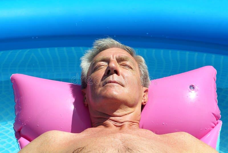 Älterer Mann, der auf einem lilo ein Sonnenbad nimmt stockbild