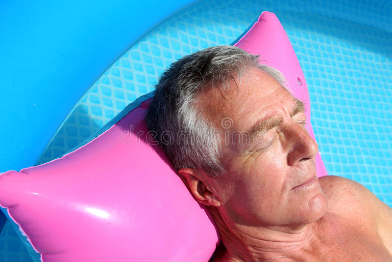 Älterer Mann, der auf einem lilo ein Sonnenbad nimmt stockfotos