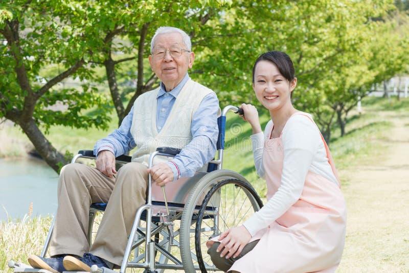 Älterer Mann, der auf einem Rollstuhl mit Pflegekraft sitzt stockfoto