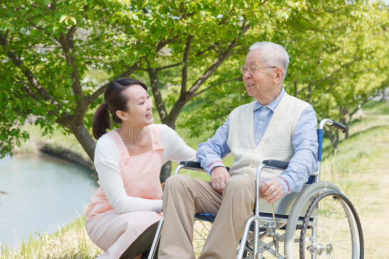 Älterer Mann, der auf einem Rollstuhl mit Pflegekraft sitzt stockbild