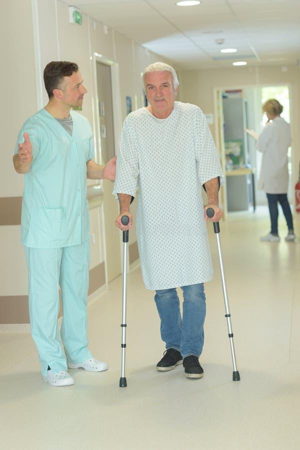 Älterer Mann, der auf Krücken im Krankenhauskorridor geht lizenzfreies stockbild