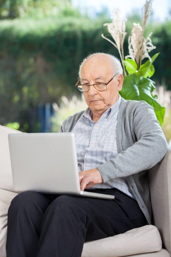 Älterer Mann, der auf Laptop surft stockfotos