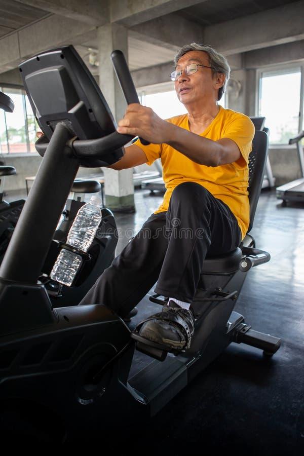 Älterer älterer Mann, der auf der Radfahrenmaschine sich entspannt in der Eignungsturnhalle trainiert gealtert Altes männliches T stockfotos