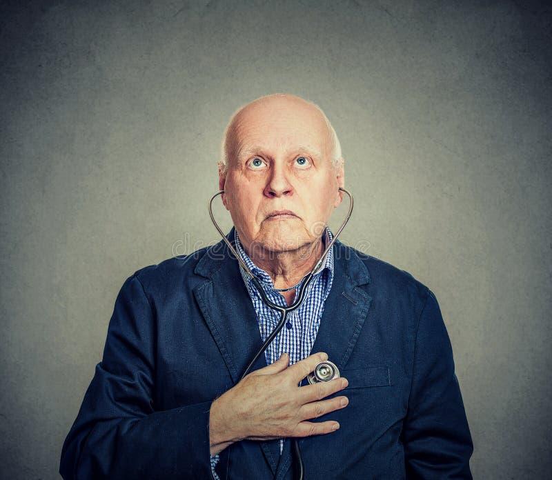 Älterer Mann, der auf sein Herz mit Stethoskop hört stockfoto