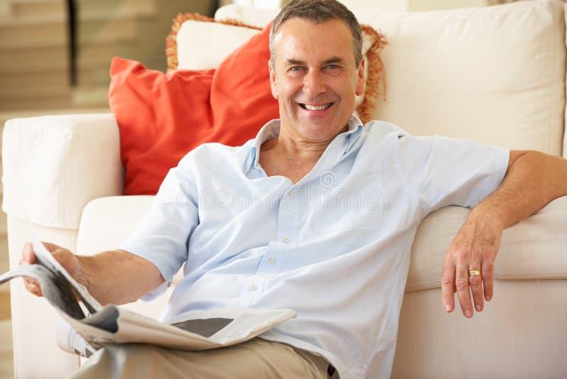 Älterer Mann, der auf Sofa sich entspannt lizenzfreies stockfoto