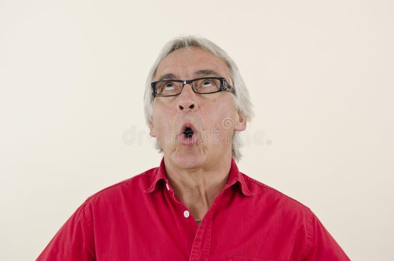 Älterer Mann, der aufwärts überrascht schaut stockfoto