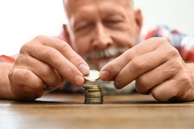 Älterer Mann, der bei Tisch herauf Münzen, Fokus an stapelt lizenzfreies stockfoto