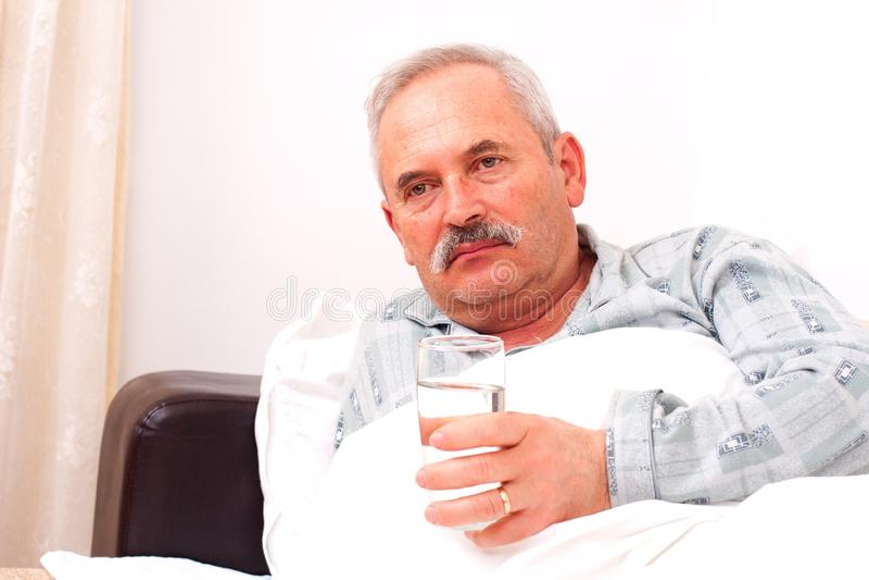 Älterer Mann, der in Bett legt stockbild