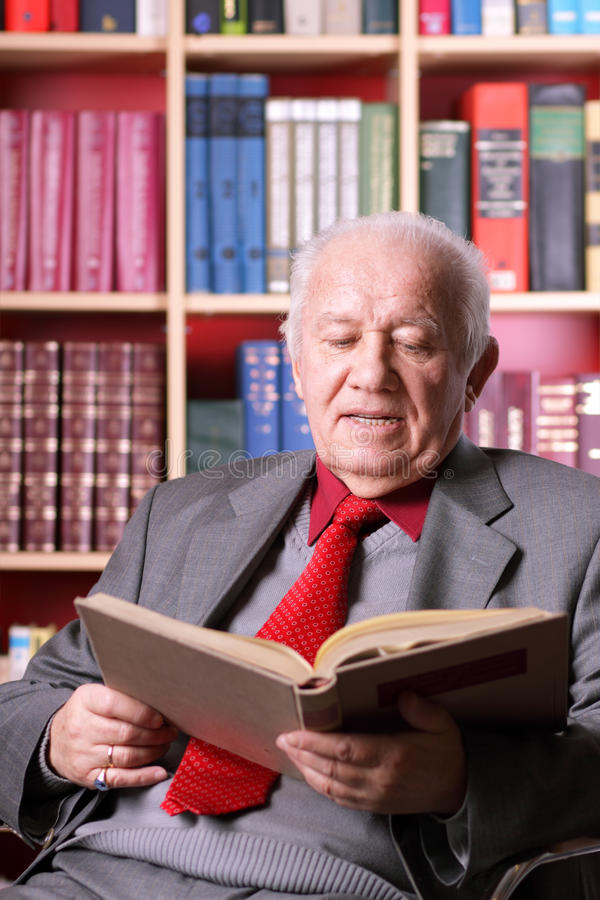 Älterer Mann in der Bibliothek stockbild
