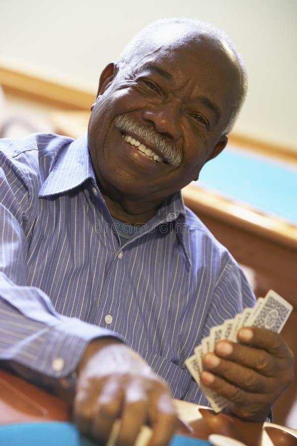 Älterer Mann, der Brücke spielt lizenzfreies stockbild
