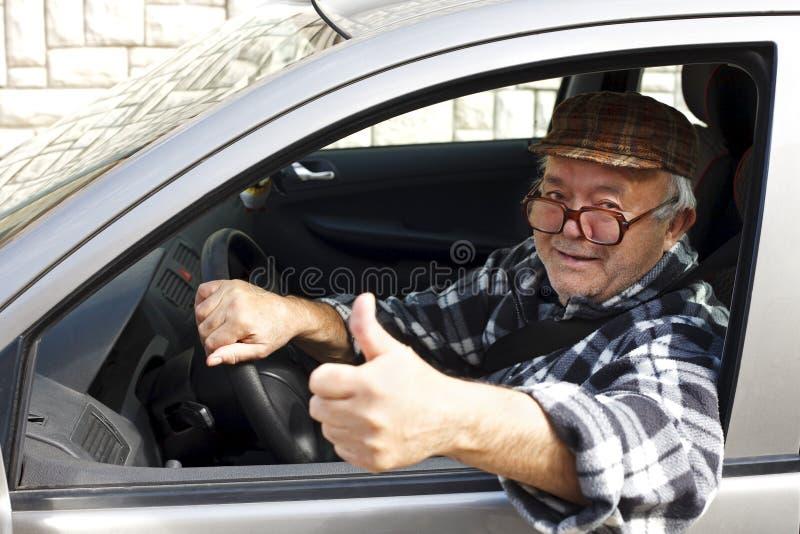 Älterer Mann, der das Auto und die Shows der Daumen fährt stockfoto