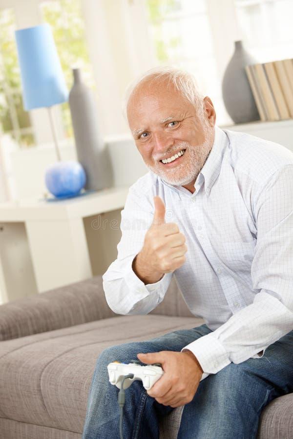 Älterer Mann, der Daumen mit Computerspiel aufgibt lizenzfreie stockfotos