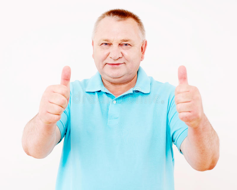 Älterer Mann, der Daumen oben über Weiß zeigt stockbilder