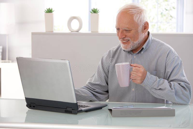 Älterer Mann, der an dem Laptoplächeln arbeitet stockfotos
