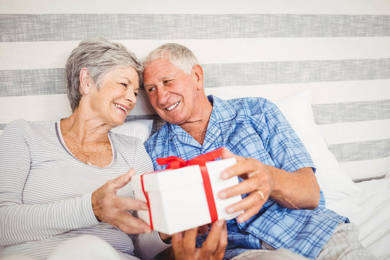 Älterer Mann, der der älteren Frau ein Überraschungsgeschenk gibt stockfoto