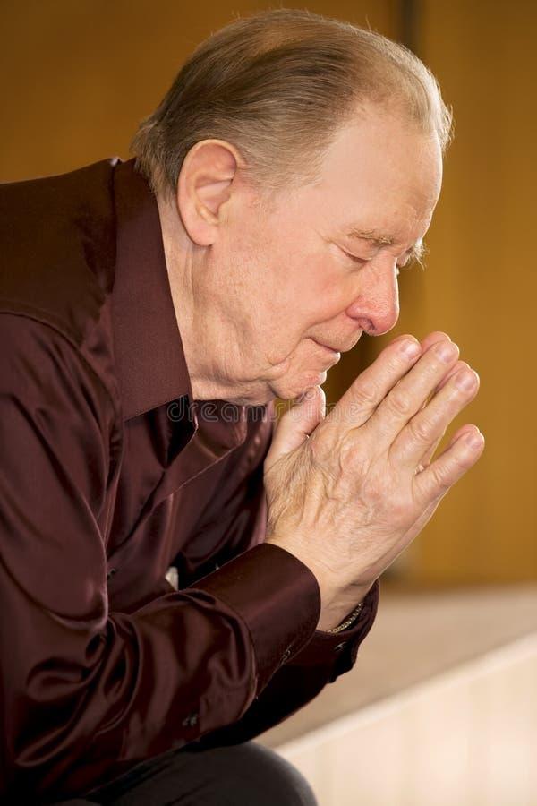 Älterer Mann, der in der Kirche betet lizenzfreie stockfotos