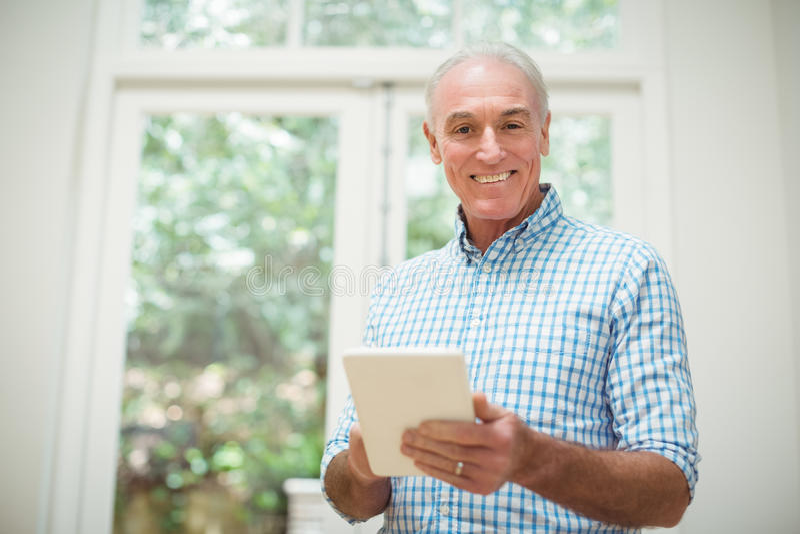 Älterer Mann, der digitale Tablette im Wohnzimmer verwendet lizenzfreie stockfotografie