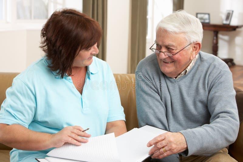 Älterer Mann in der Diskussion mit Gesundheits-Besucher bei Ho lizenzfreie stockfotografie