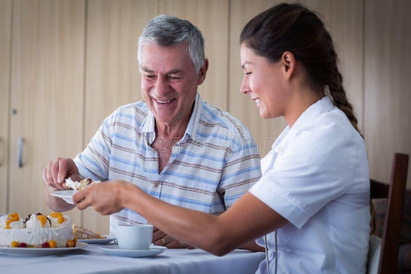 Älterer Mann, der Doktor im Wohnzimmer Kuchen gibt lizenzfreie stockfotografie