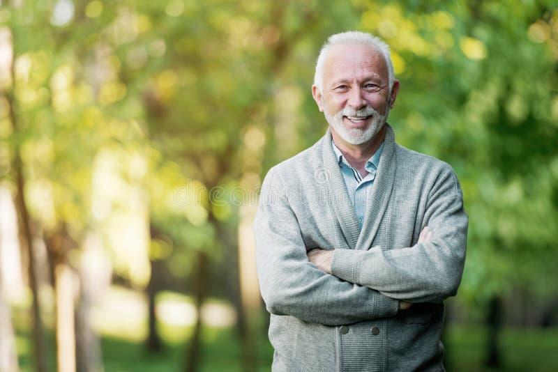 Älterer Mann, der draußen in der Natur lächelt lizenzfreies stockbild