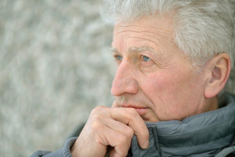 Älterer Mann, der draußen steht stockfoto