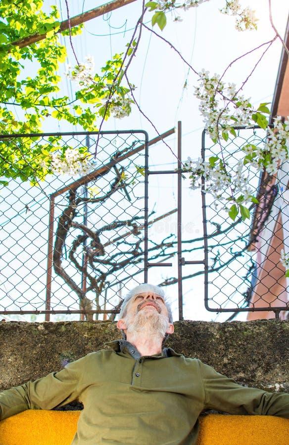 Älterer Mann, der draußen Zeit genießt stockbild