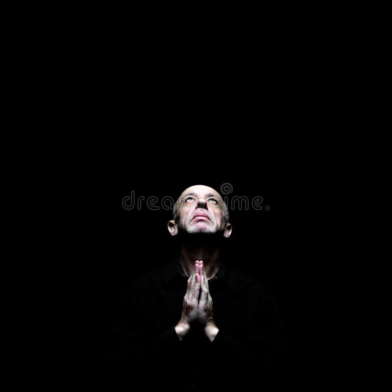 Älterer Mann, der in der Dunkelheit praing ist stockbilder