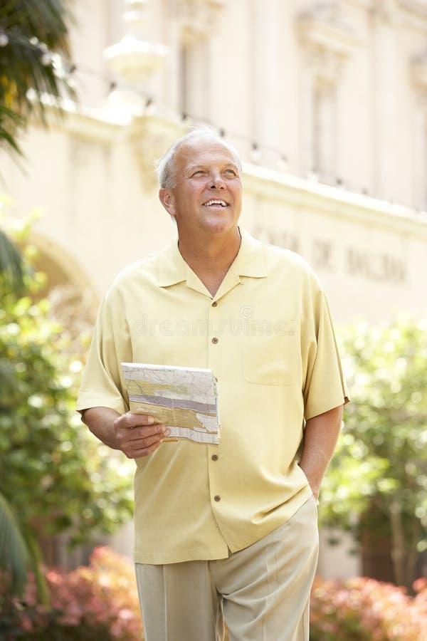 Älterer Mann, der durch Stadt-Straße mit Karte geht lizenzfreies stockbild