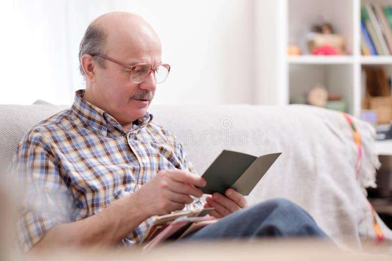 Älterer Mann, der ein Buch auf seinem Sofa liest stockbilder