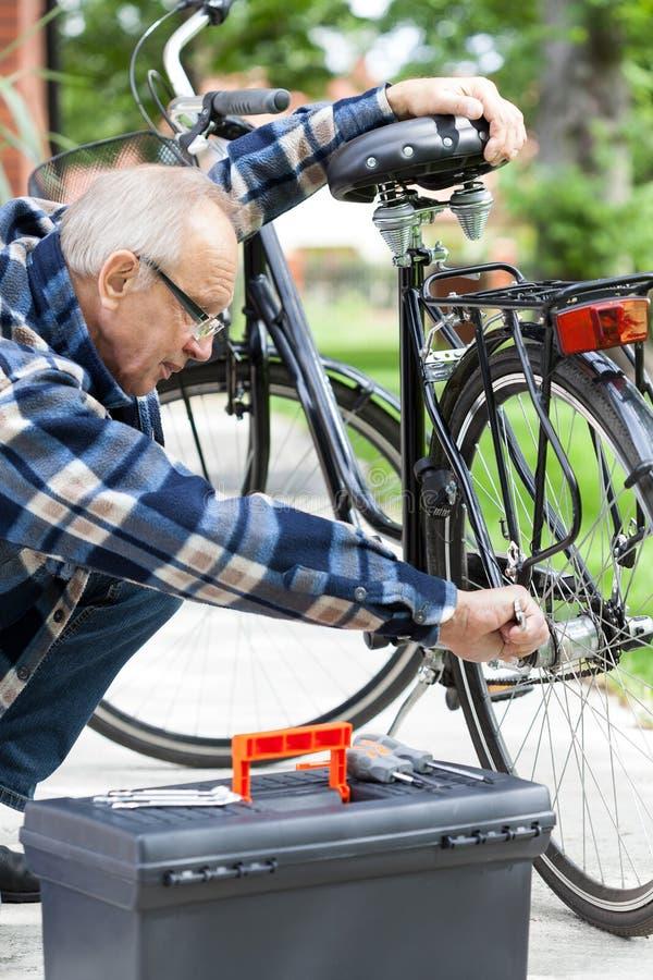 Älterer Mann, der ein Fahrrad repariert lizenzfreie stockfotos