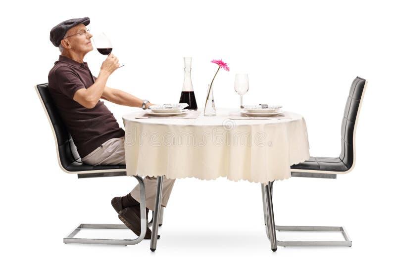 Älterer Mann, der ein Glas Wein riecht lizenzfreie stockfotografie