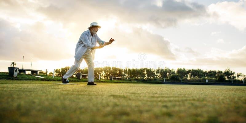 Älterer Mann, der ein Spiel von Boules spielt lizenzfreies stockfoto