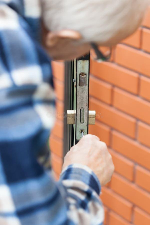Älterer Mann, der ein Türschloss repariert stockfoto
