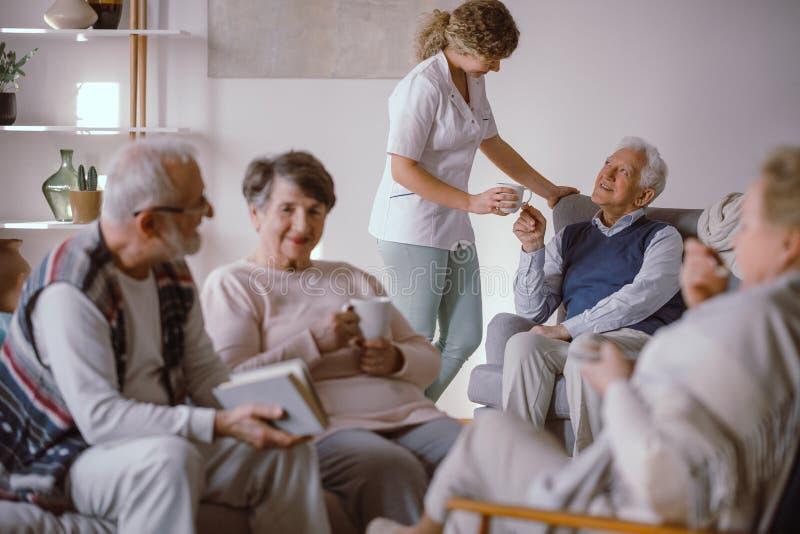Älterer Mann, der eine Tasse Tee von seiner Pflegekraft im Pflegeheim nimmt lizenzfreie stockbilder
