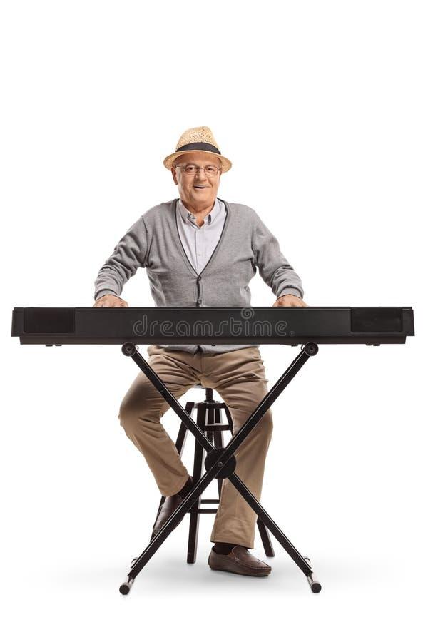 Älterer Mann, der eine Tastatur sitzt und spielt stockfotos