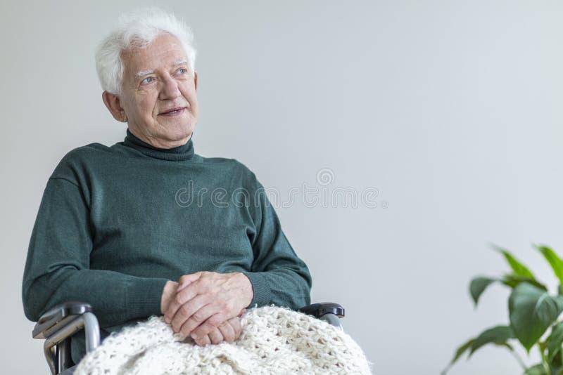 Älterer Mann, der in einem Rollstuhl sitzt und an gute Zeiten denkt Setzen Sie Ihr Plakat stockfotografie