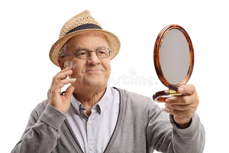 Älterer Mann, der in einem Spiegel betrachtet und sein Gesicht berührt lizenzfreie stockfotos