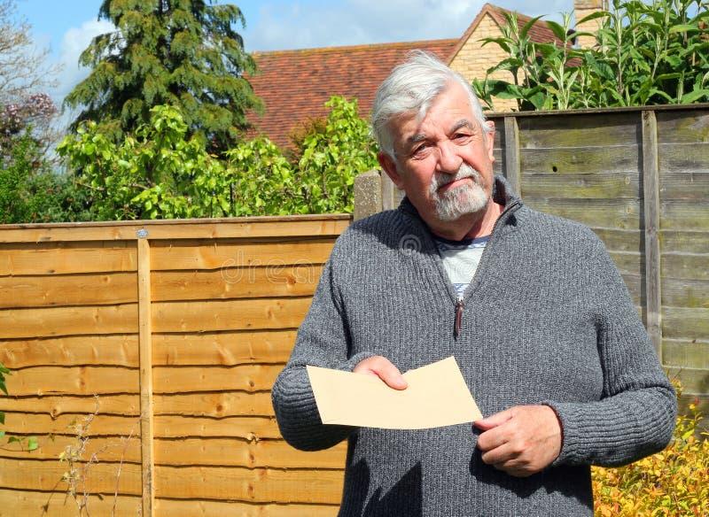 Älterer Mann, der einen einfachen braunen Umschlag gibt lizenzfreie stockfotografie