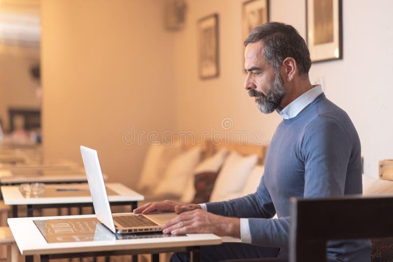 Älterer Mann, der einen Laptop in einer Kaffeestube verwendet lizenzfreies stockfoto