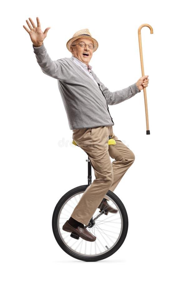 Älterer Mann, der einen Mono-zyklus reitet und einen gehenden Stock hält stockfoto