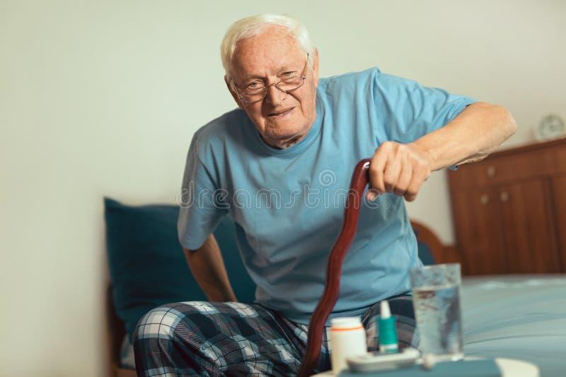 Älterer Mann, der einen Spazierstock hält lizenzfreie stockfotos