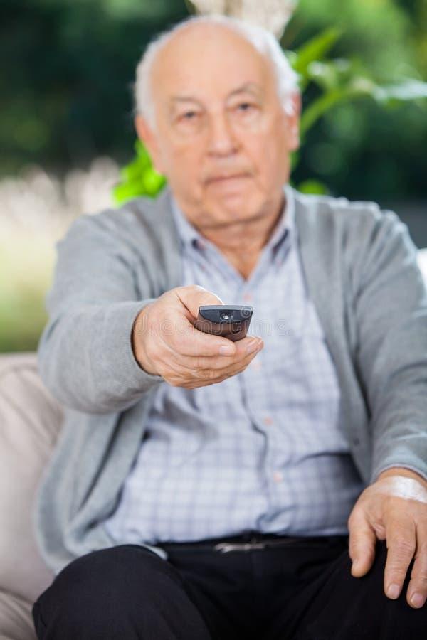 Älterer Mann, der Fernbedienung beim an sitzen verwendet stockfotografie