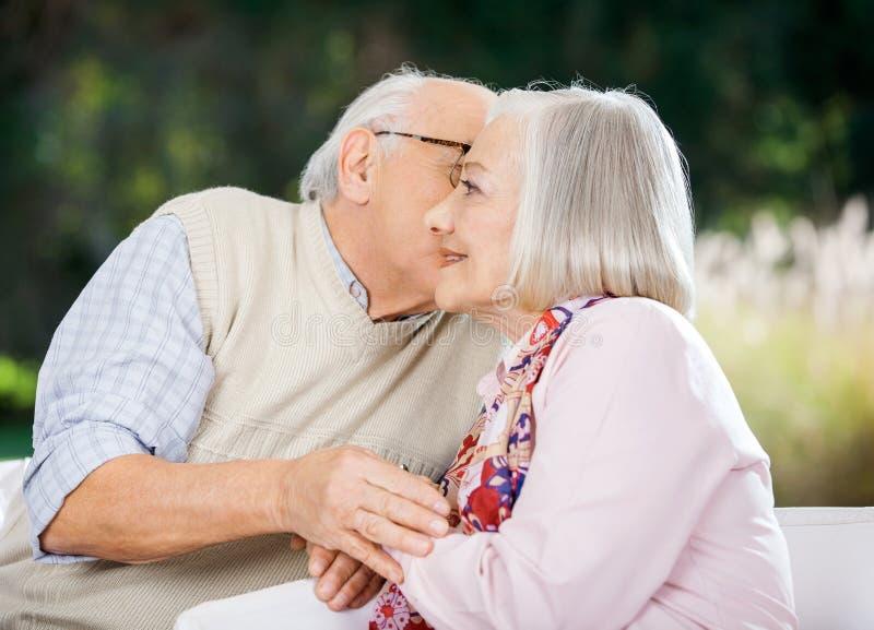 Älterer Mann, der Frau küsst lizenzfreie stockfotografie