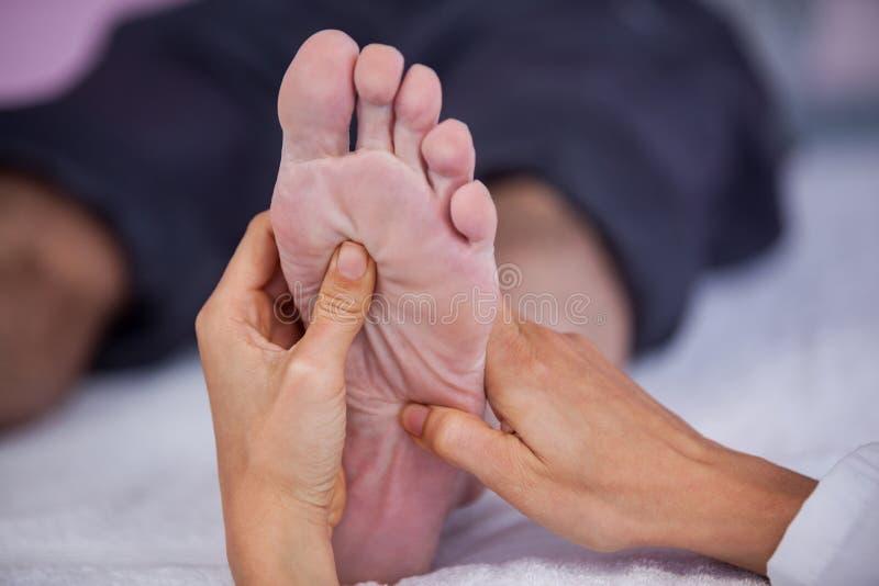 Älterer Mann, der Fußmassage vom Physiotherapeuten empfängt lizenzfreie stockbilder