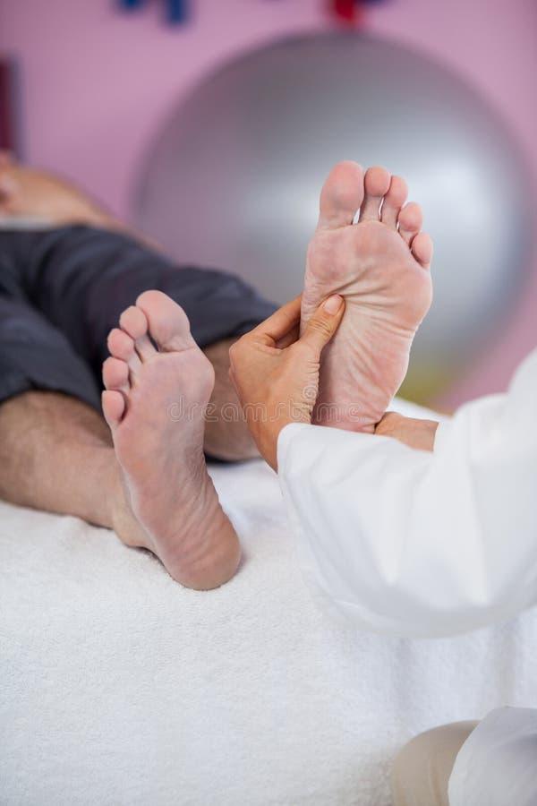 Älterer Mann, der Fußmassage vom Physiotherapeuten empfängt stockbild