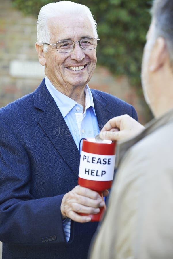 Älterer Mann, der Geld für Nächstenliebe sammelt lizenzfreies stockfoto