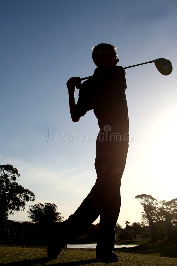 Älterer Mann, der Golfball antreibt stockfotos