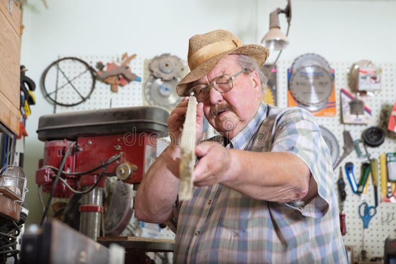 Älterer Mann, der hölzerne Planke anhält stockbilder